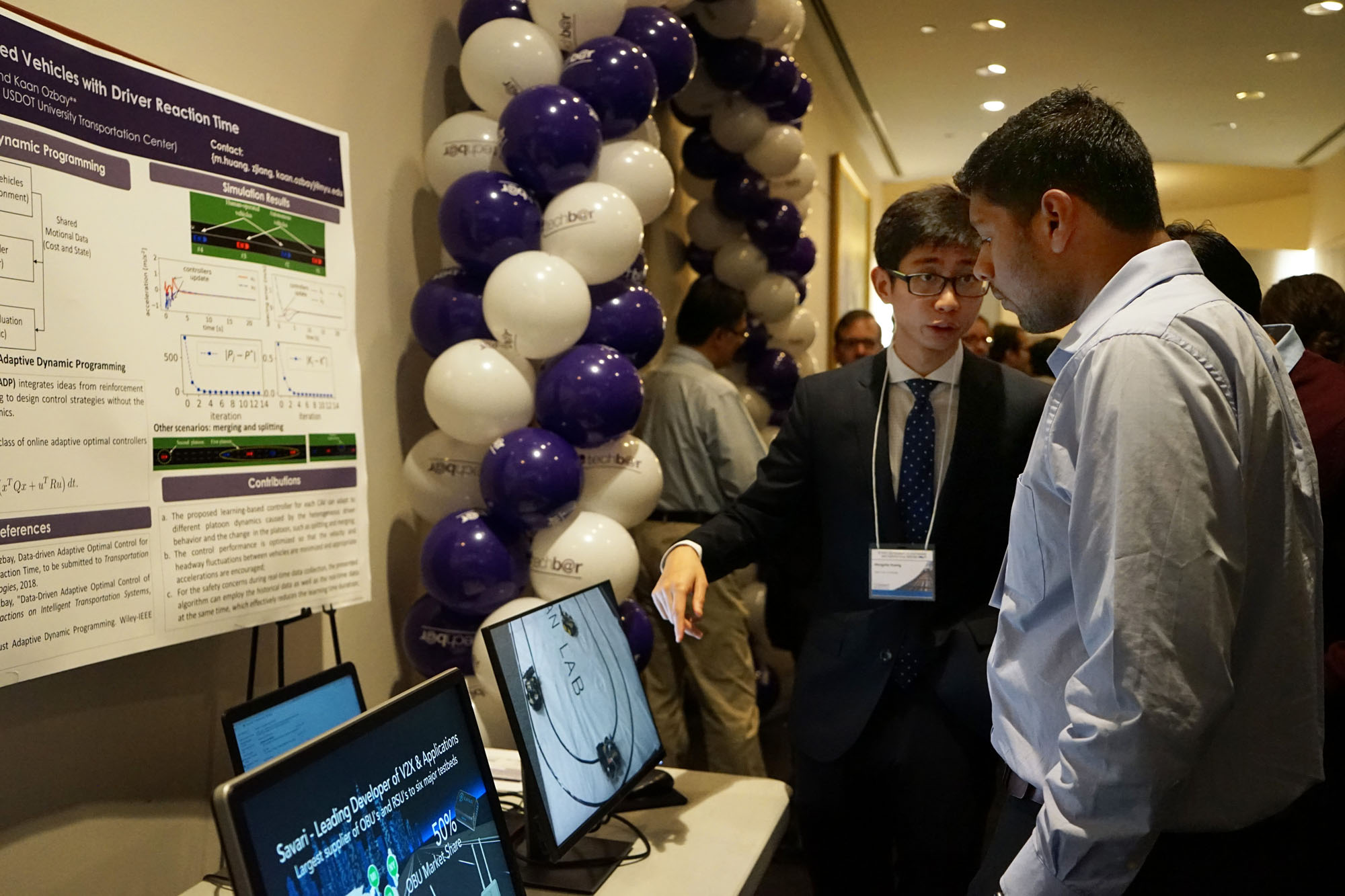 NYU Tandon PhD candidate Mengzhe Huang explains some of the recent research on display to a symposium attendee.