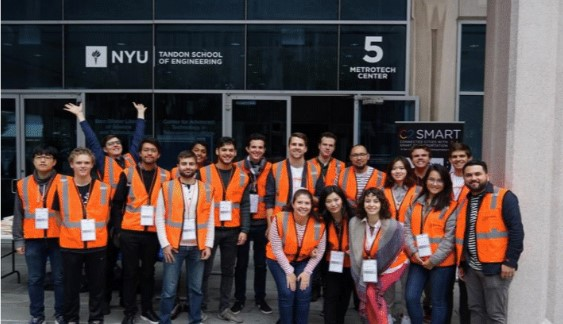 All the volunteers for Transportation Camp pose in orange safety vests for the camera