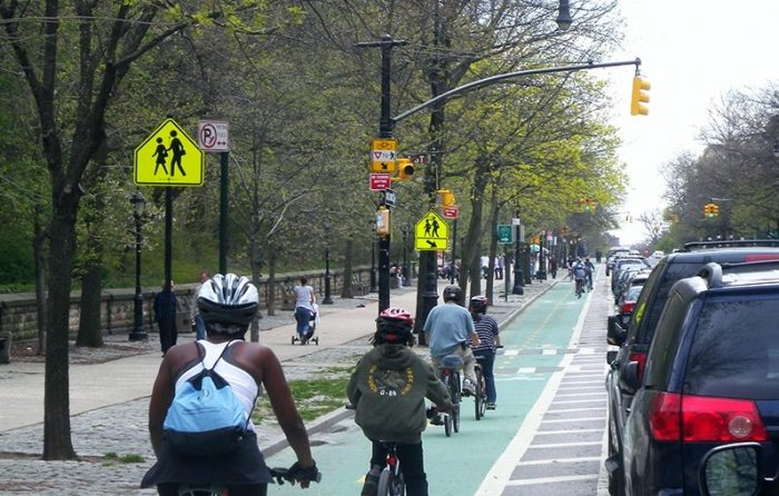 Cyclists using a green cycling lane on a NYC street