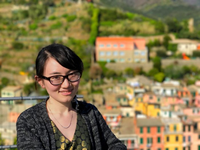 Head shot of woman with neighborhood of foreign country in background